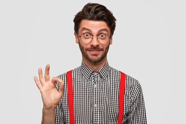 Belo jovem empresário com barba por fazer mostra que está tudo bem com a mão, acalma e fala pra você