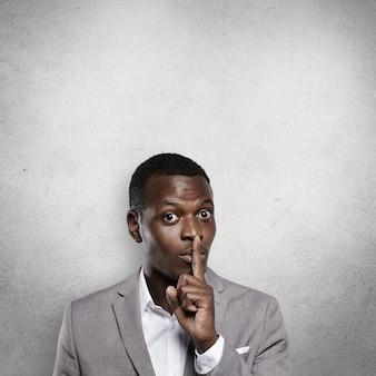Belo jovem empresário de pele escura em um terno cinza formal gesticulando como se pedisse para não contar a ninguém sobre seu segredo comercial, segurando o dedo indicador nos lábios e dizendo: shh