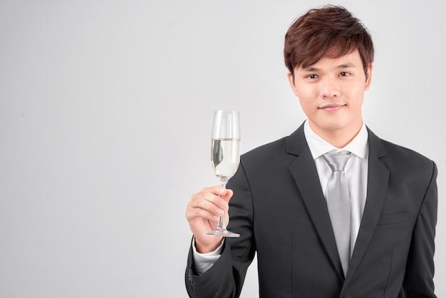 Belo jovem empresário de terno e gravata aplausos com taça de champanhe sobre fundo branco
