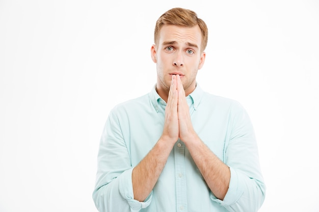 Belo jovem empresário em pé e orando
