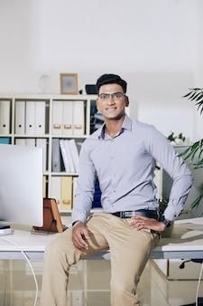Belo jovem empresário indiano sentado na ponta da mesa do escritório e sorrindo para a câmera