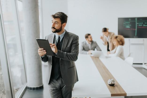 Belo jovem empresário moderno usando tablet digital no escritório