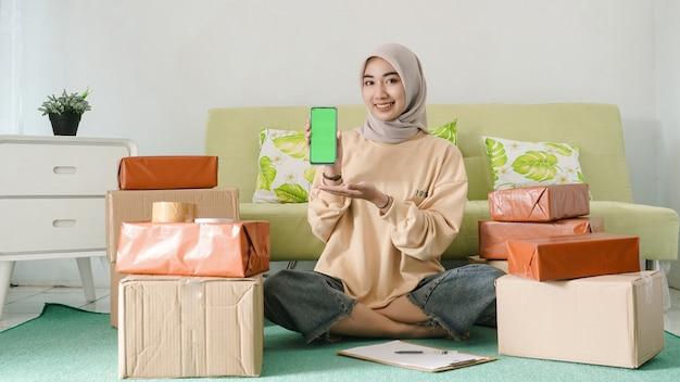Belo jovem empresário mostrando a tela do smartphone