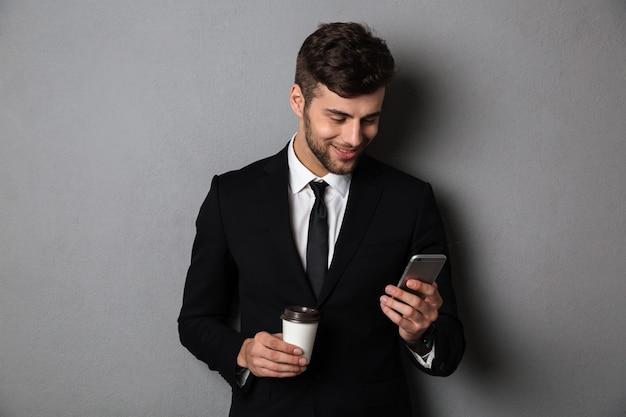 Belo jovem homem com roupa formal, verificando notícias no smartphone enquanto segura o café para viagem