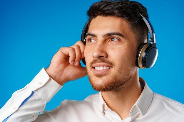 Belo jovem mestiço ouvindo música com fones de ouvido azuis close-up
