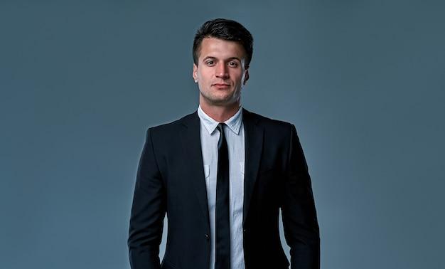 Belo jovem modelo moreno, vestindo terno preto e branco, olhando com atitude, posando no estúdio, isolado no fundo cinza. retrato de homem de negócios. copie o espaço. visualização horizontal.