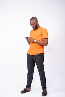 Belo jovem negro usando seu smartphone, mensagens de texto e conceito on-line de bate-papo nas redes sociais, navegando Foto Premium