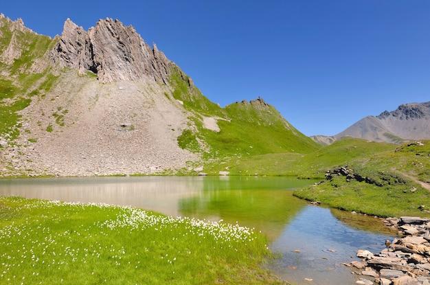 Belo lago alpino com vegetação e montanha rochosa sob o azul