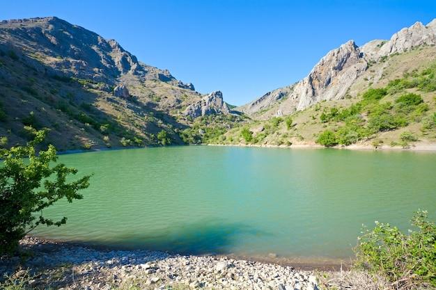 Belo lago e montanha de rochas de verão atrás (vila de zelenogorye, crimeia, ucrânia)