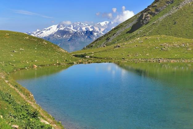 Belo lago em um lago de montanha alpina com fundo de montanha de pico nevado