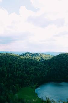 Belo lago rodeado por colinas cobertas de árvores sob o céu nublado