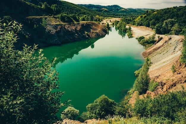 Belo lago verde de forma alongada, com costa rochosa de pedra esmagada, rodeada por vegetação. pedreira profunda inundada para extração de minerais.