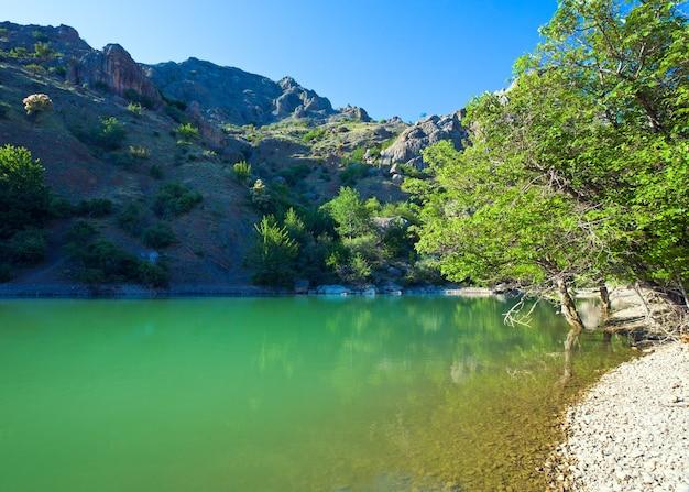 Belo lago verde-esmeralda e montanha de rochas de verão atrás (zelenogorye (vila de green mountains, crimeia, ucrânia)