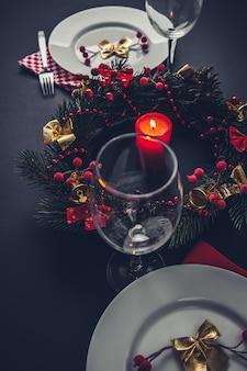 Belo local de jantar de natal para dois. mesa decorada com uma coroa de flores e uma vela.