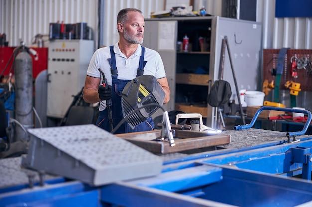 Belo mecânico segurando uma tocha de soldagem e um capacete de soldagem