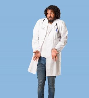 Belo médico americano africano duvidando e encolher os ombros os ombros