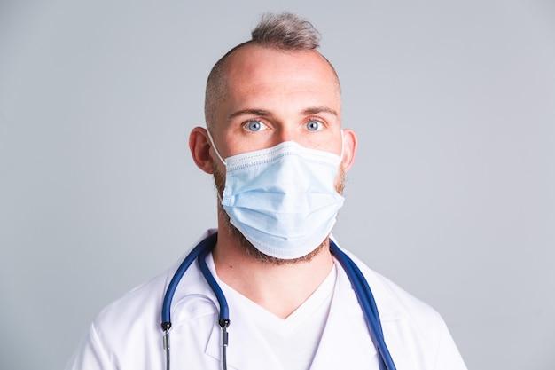 Belo médico masculino na parede cinza com máscara médica protetora no rosto