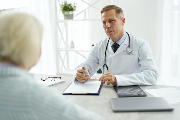 Belo médico masculino, tendo uma consulta com o paciente na clínica