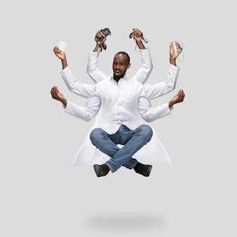Belo médico multiarmed levitando isolado no fundo cinza do estúdio com equipamento