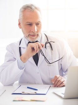 Belo médico no jaleco branco está usando um laptop.