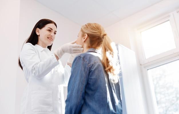 Belo médico simpático e positivo em pé na frente de sua paciente e olhando para ela enquanto faz um exame médico