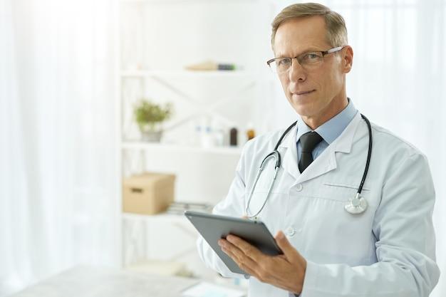 Belo médico vestindo jaleco usando computador tablet na clínica