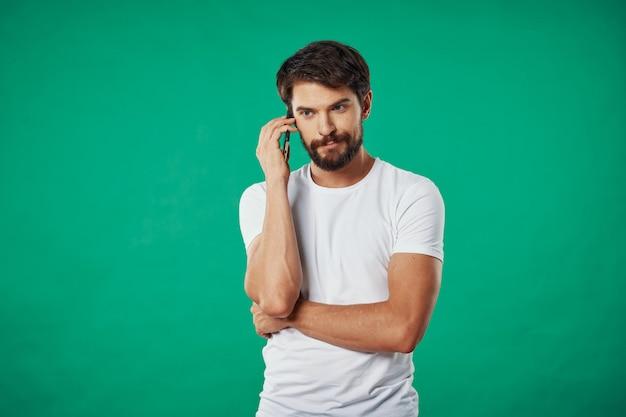 Belo modelo masculino com barba com um telefone posando em