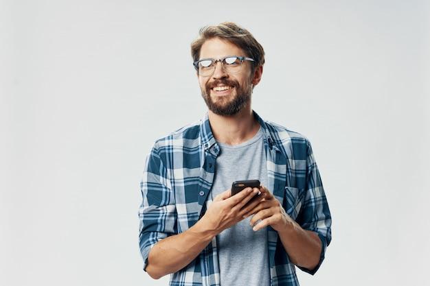Belo modelo masculino com barba com um telefone posando no estúdio