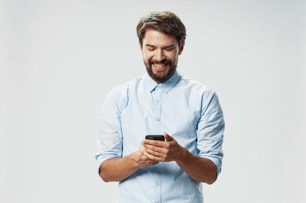 Belo modelo masculino com barba com um telefone