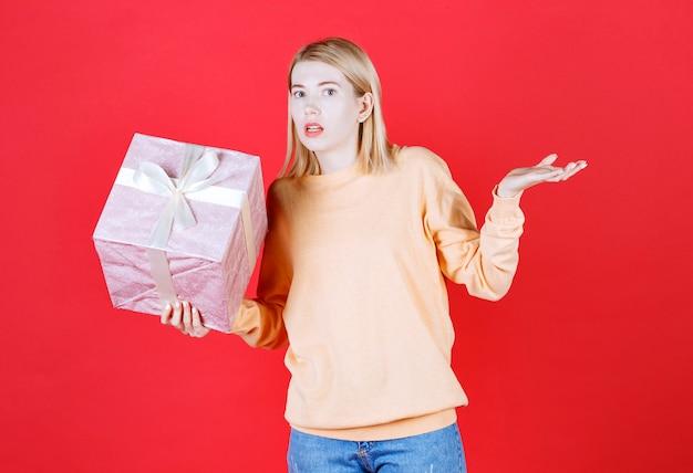 Belo modo feminino fazendo sinal com a mão enquanto segura a caixa de presente na frente da parede vermelha