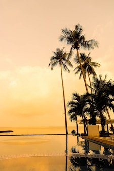 Belo nascer do sol com silhueta palmeira de coqueiro e piscina de cadeiras em volta da piscina no lindo resort hoteleiro de luxo - vintage filter