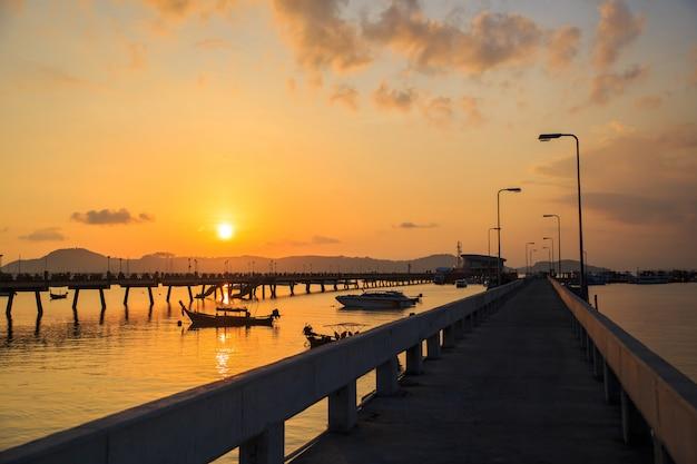 Belo nascer do sol e paisagens do concreto ponte pier com barcos durante o nascer do sol verão viajar em phuket