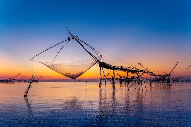 Belo nascer do sol e redes de mergulho de pesca em pakpra em phatthalung, tailândia.