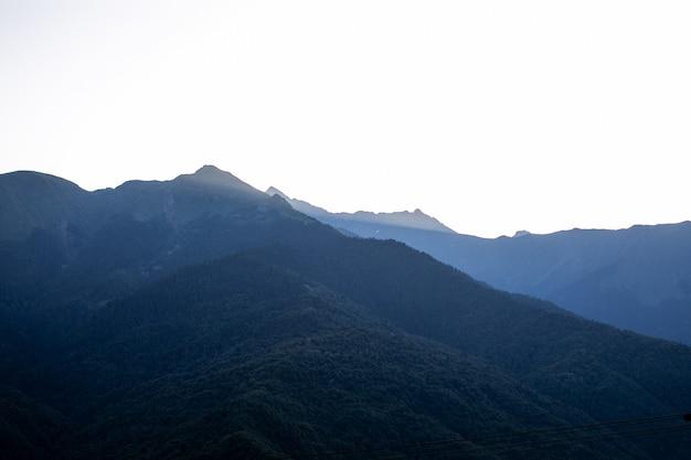 Belo nascer do sol no céu claro de manhã com raios e silhueta de montanha