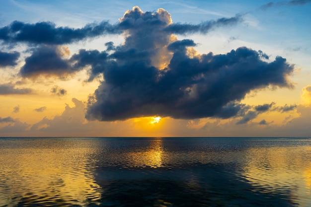 Belo nascer do sol sobre o oceano índico, na ilha de zanzibar, tanzânia, áfrica oriental. conceito de viagens e natureza. céu matinal, nuvens, sol e água do mar