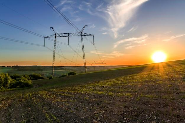Belo panorama amplo de linhas de alta tensão e postes de energia que se estendem através de campos de primavera verde tranquila e floresta ao amanhecer ou pôr do sol com sol branco brilhante no horizonte laranja sob o céu azul claro.