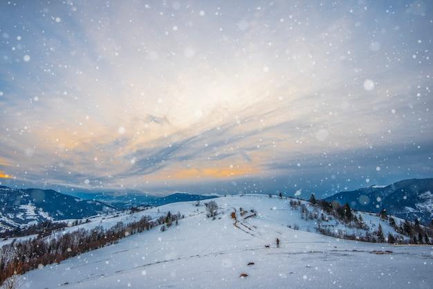 Belo panorama das cordilheiras cobertas de neve e divididas em trilhas com vista para o céu nublado e o pôr do sol