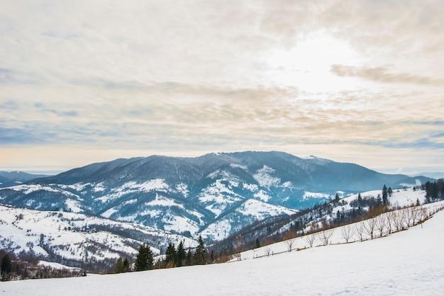 Belo panorama das encostas das montanhas com trilhas com vista para as colinas e florestas de coníferas nubladas e geladas em uma noite de inverno. turismo de inverno e conceito de lazer.