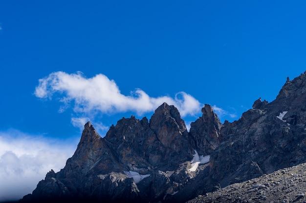 Belo panorama de altas montanhas rochosas contra o céu azul e nuvens