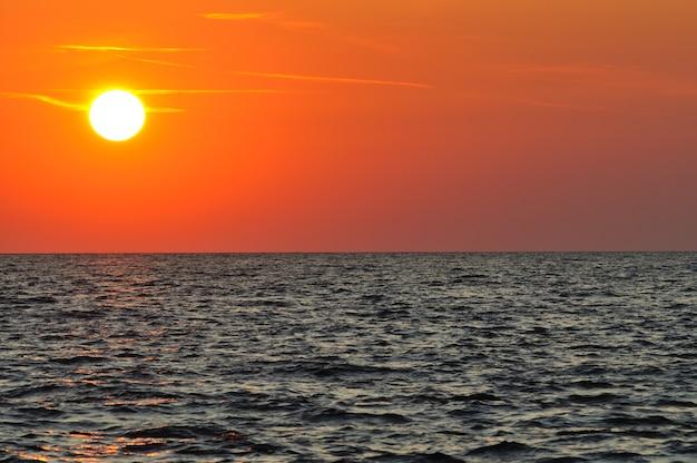 Belo pôr do sol colorido sobre as águas onduladas do mar negro, na crimeia, num dia de verão.