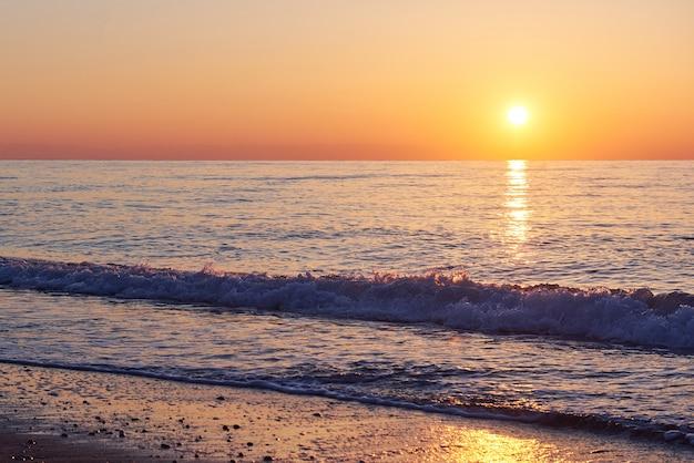 Belo pôr do sol colorido sobre o mar e o sol brilha. céu laranja.