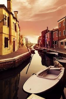 Belo pôr do sol com barcos, edifícios e água. luz solar. toning. burano, itália.