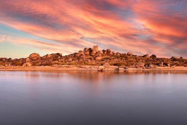 Belo pôr do sol com céu laranja na margem de um lago