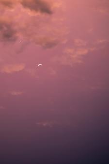 Belo pôr do sol com lua e estrela no céu nublado
