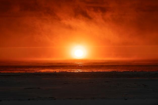 Belo pôr do sol com nevoeiro no mar ártico.
