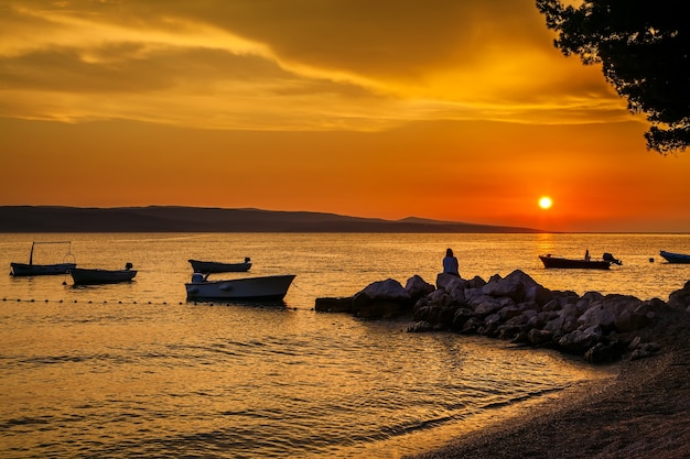 Belo pôr do sol com os barcos e a mulher sentada nas pedras, croácia