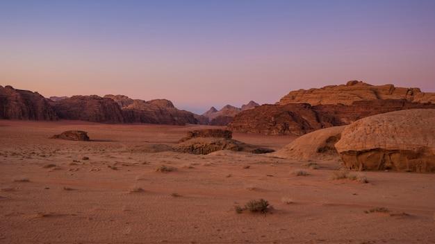 Belo pôr do sol com vista para as montanhas no deserto de wadi rum na jordânia