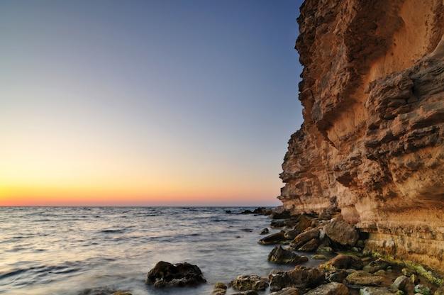 Belo pôr do sol-de-rosa, pedras de pedra e água com paisagem verde musgo