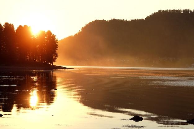 Belo pôr do sol de verão no lago, raios de sol