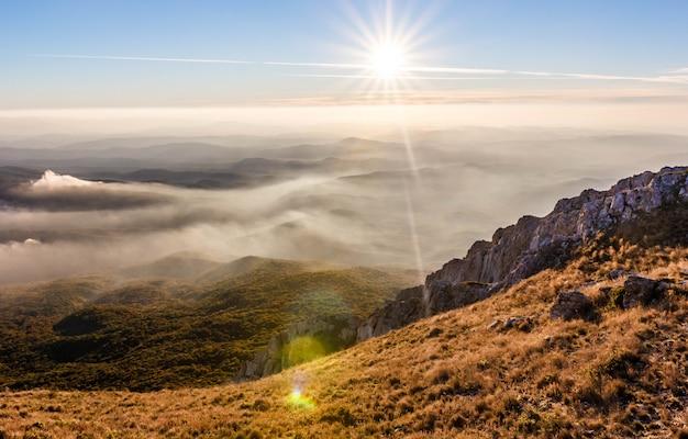 Belo pôr do sol dourado nas montanhas com nuvens baixas.